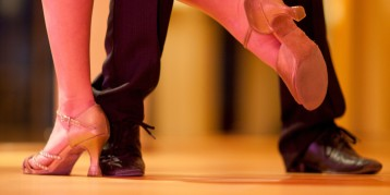 Ballroom dancers in dance studio, low section